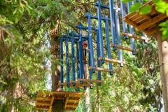 Tienerjongen op een kabelscursus in een treetop avonturenpark die hangende kabelhindernis overgaan royalty-vrije stock afbeeldingen