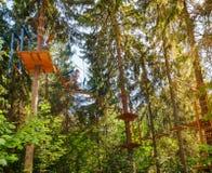 Tienerjongen op een kabelscursus in een treetop avonturenpark die hangende kabelhindernis overgaan stock foto