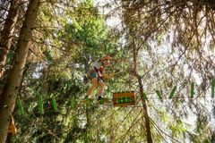 Tienerjongen op een kabelscursus in een treetop avonturenpark die hangende kabelhindernis overgaan royalty-vrije stock afbeelding