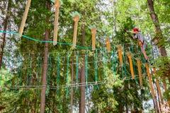Tienerjongen op een kabelscursus in een treetop avonturenpark die hangende kabelhindernis overgaan royalty-vrije stock fotografie