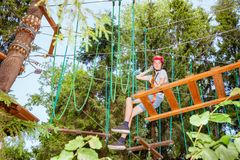 Tienerjongen op een kabelscursus in een treetop zitting van het avonturenpark op een hangende kabelbrug stock fotografie