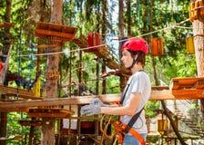 Tienerjongen zelf dragen maakt veiligheidsmateriaal vast die een kabelscursus in een treetop avonturenpark ingaan stock afbeelding