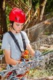 Tienerjongen zelf plaatsen maakt veiligheidsmateriaal bij een kabelscursus in vast een treetop avonturenpark stock foto's