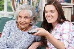 Tienerkleindochter het Letten op Televisie met Grootmoeder stock fotografie