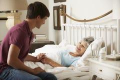 Tienerkleinzoon Bezoekende Grootmoeder in Bed thuis stock foto