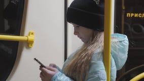 Tienerlezing van het mobiele telefoonscherm in metro stock footage