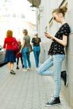 Tienermeisje dat tegen de muur leunt en celtelefoon met behulp van stock afbeelding