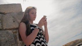 Tienermeisje die aan muziek met hoofdtelefoons op smartphone op een achtergrond van overzees en de ruïnes van de oude stad luiste stock videobeelden