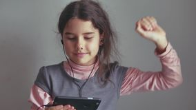 Tienermeisje die aan muziek op hoofdtelefoons luisteren en op een smartphone dansen royalty-vrije stock foto's