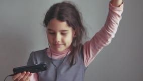 Tienermeisje die aan muziek op hoofdtelefoons luisteren en op een smartphone dansen stock fotografie