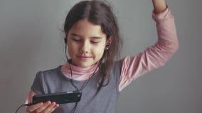 Tienermeisje die aan muziek op hoofdtelefoons luisteren en op een smartphone dansen royalty-vrije stock afbeelding