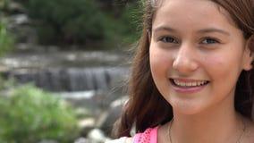 Tienermeisje die bij Cascade glimlachen stock videobeelden