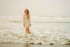 Tienermeisje die in de golven wandelen Royalty-vrije Stock Afbeeldingen