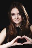 Tienermeisje die de liefdesymbool van de hartvorm met handen doen Stock Fotografie
