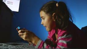 Tienermeisje die draagbaar jong geitje video online spel binnen spelen een consolejong geitje bij nacht stock footage