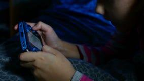 Tienermeisje die draagbaar video online jong geitjespel binnen spelen een consolejong geitje bij nacht stock video