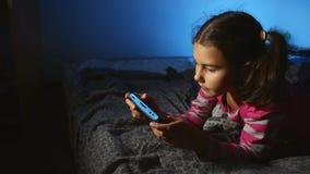 Tienermeisje die draagbaar videospelletje binnen spelen een console online jong geitje bij nacht stock videobeelden