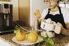 Tienermeisje die een citrusvrucht juicer met oranje en verse citrusvruchten in de keuken houden royalty-vrije stock fotografie