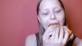 Tienermeisje die een hamburger eten stock videobeelden
