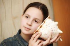 Tienermeisje die een zeeschelp toepassen op zijn oor het luisteren stock foto's