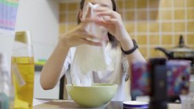 Tienermeisje die en met eigengemaakt wit slijm drukken spelen stock footage