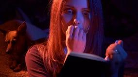 Tienermeisje die eng boek lezen bij nacht stock footage