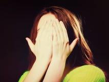 Tienermeisje die haar gezicht behandelen met handen op zwarte royalty-vrije stock foto