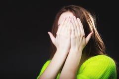 Tienermeisje die haar gezicht behandelen met handen op zwarte royalty-vrije stock afbeeldingen