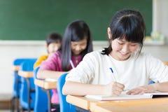 tienermeisje die in het klaslokaal leren stock foto's