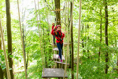 Tienermeisje die in hoge kabelcursus beklimmen of parl Stock Afbeelding