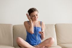 Tienermeisje die hoofdtelefoons dragen die van muziek op mobiele telefoon genieten appl Royalty-vrije Stock Afbeeldingen
