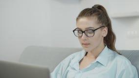 Tienermeisje die laptop met behulp van thuis, typend op notitieboekje, voorbereidingen treffend voor examens of thuiswerk stock video