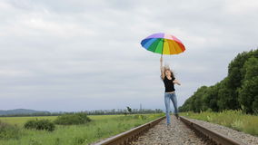 Tienermeisje die met paraplu op de spoorweg springen stock videobeelden