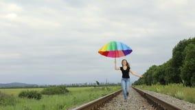 Tienermeisje die met paraplu op de spoorweg springen stock video