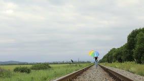 Tienermeisje die met paraplu op de spoorweg springen stock footage