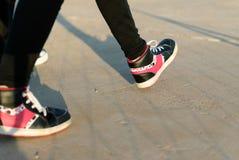 Tienermeisje die met roze tennisschoenen lopen Stock Foto's