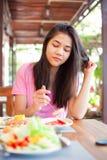 Tienermeisje die ontbijt op openluchtveranda eten Royalty-vrije Stock Foto's