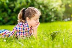 Tienermeisje die op het gras met digitale tablet liggen of eBook, openluchtportret stock afbeelding