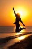 Tienermeisje die op het strand springen Stock Afbeelding