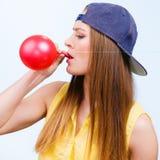 Tienermeisje die rode ballon blazen Stock Foto's