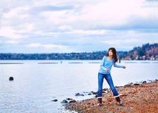 Tienermeisje die rotsen in het water, langs een rotsachtige meerkust werpen Royalty-vrije Stock Afbeeldingen
