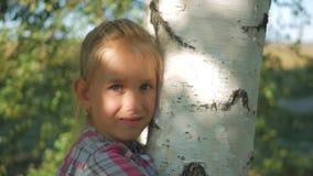 Tienermeisje die tegen een berkboom leunen in de zon Sluit omhoog, bekijkend camera stock video