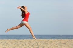 Tienermeisje in het rode springen gelukkig op het strand Stock Afbeeldingen