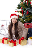 Tienermeisje in Kerstmanhoed met giften onder Kerstboom Stock Foto's