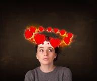 Tienermeisje met hartillustraties die rond haar hoofd circleing Stock Foto's