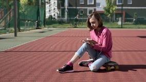 Tienermeisje met hoofdtelefoons en tablet stock videobeelden