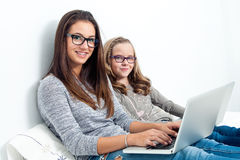 Tienermeisje met jongere zuster op bed met laptops Royalty-vrije Stock Fotografie