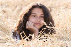 Tienermeisje met krullend donker haar op aard Stock Fotografie
