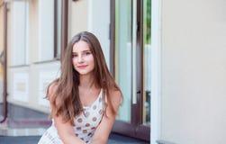 Tienermeisje met lange donkerbruine haarzitting op de marmeren stappen royalty-vrije stock afbeelding
