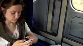 Tienermeisje met smartphone bij trein stock footage
